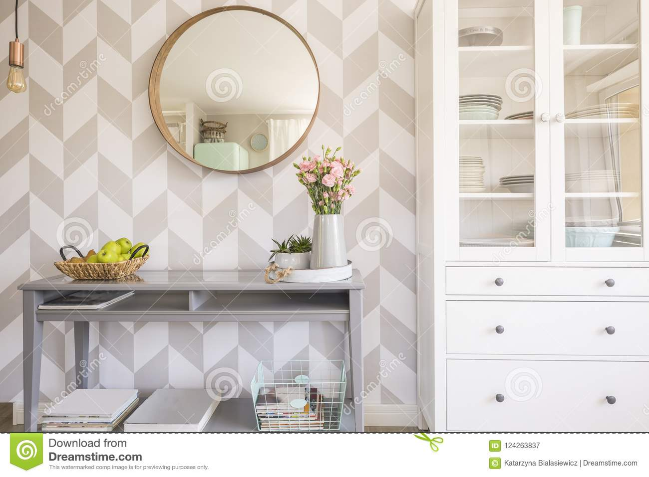 Mirror on patterned wallpaper above grey table with flowers in s