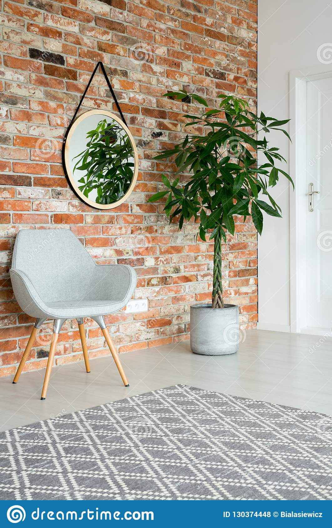Mirror on the wall of corridor with tall plant in pot, grey stylish chair and brick wall