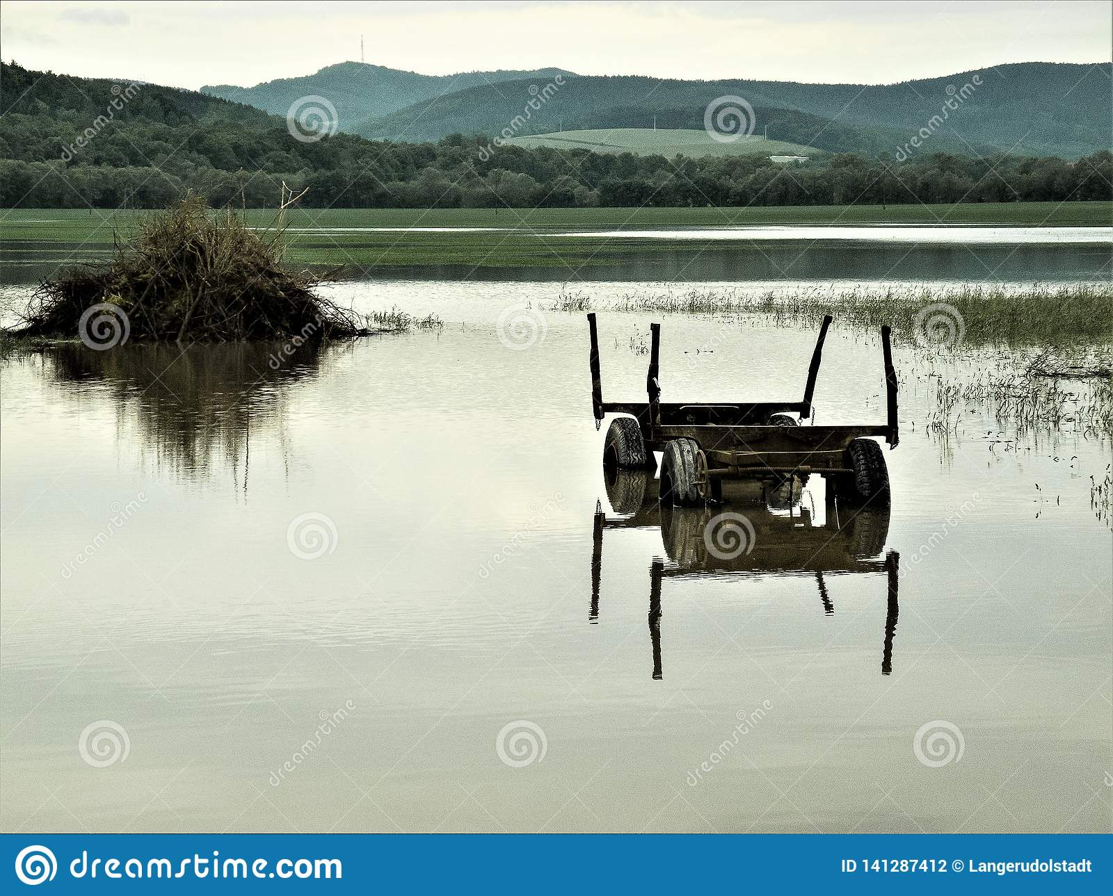 Mirroring - agricultural car in a flood area,near to Rudolstadt, Thuringia, Germany