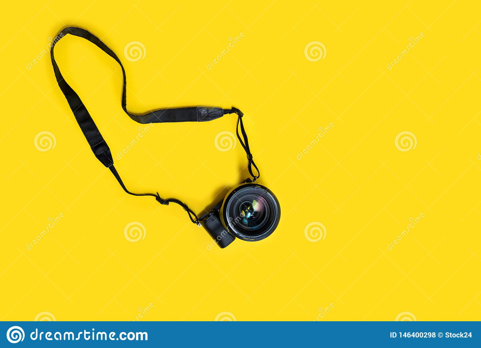 Mirrorless black camera on yellow background, summer memmories photograher blog