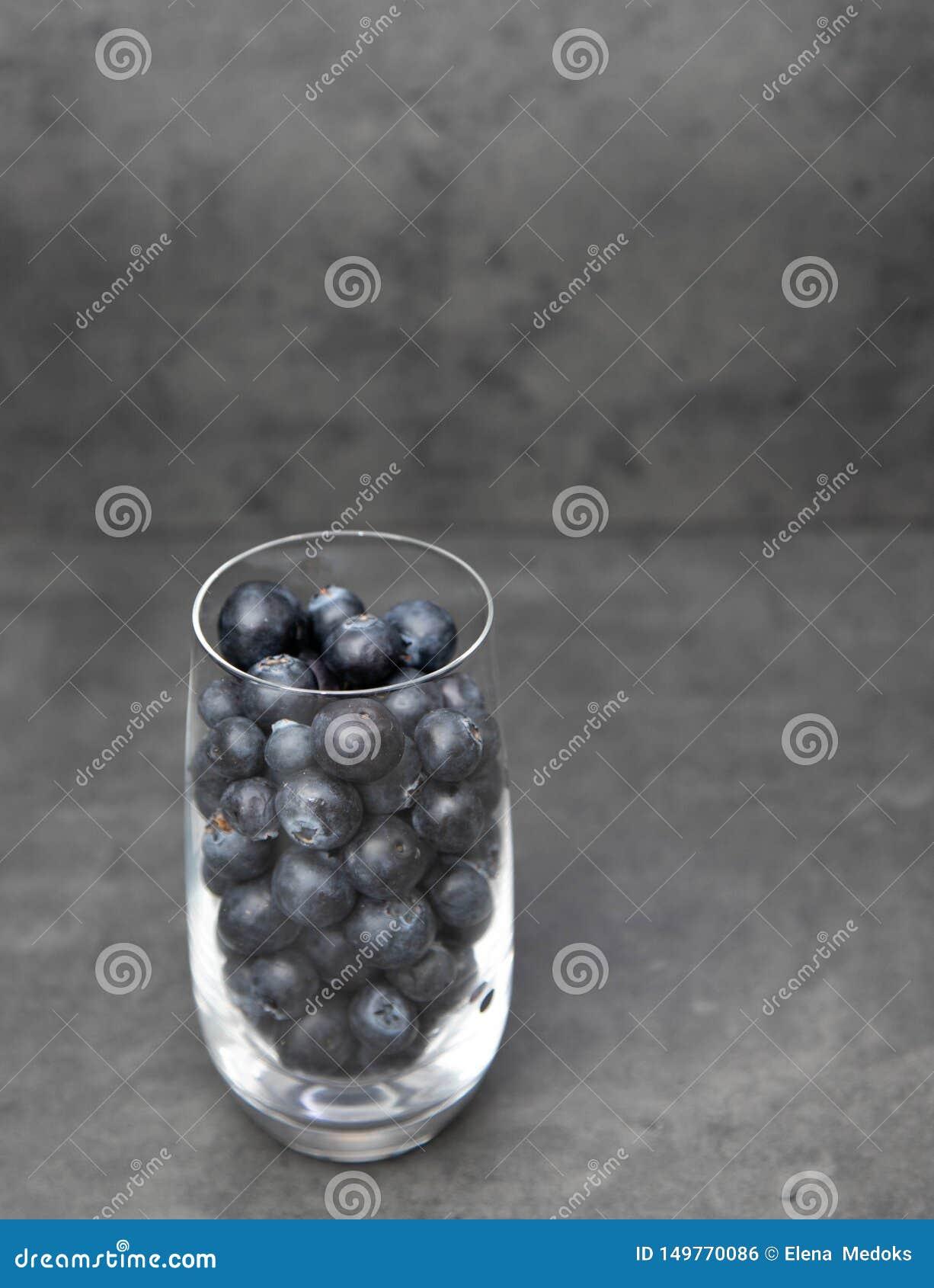 Mirtilos frescos em uma bacia de vidro Mirtilos deliciosos em um copo de vidro em um fundo cinzento Espa?o para o texto