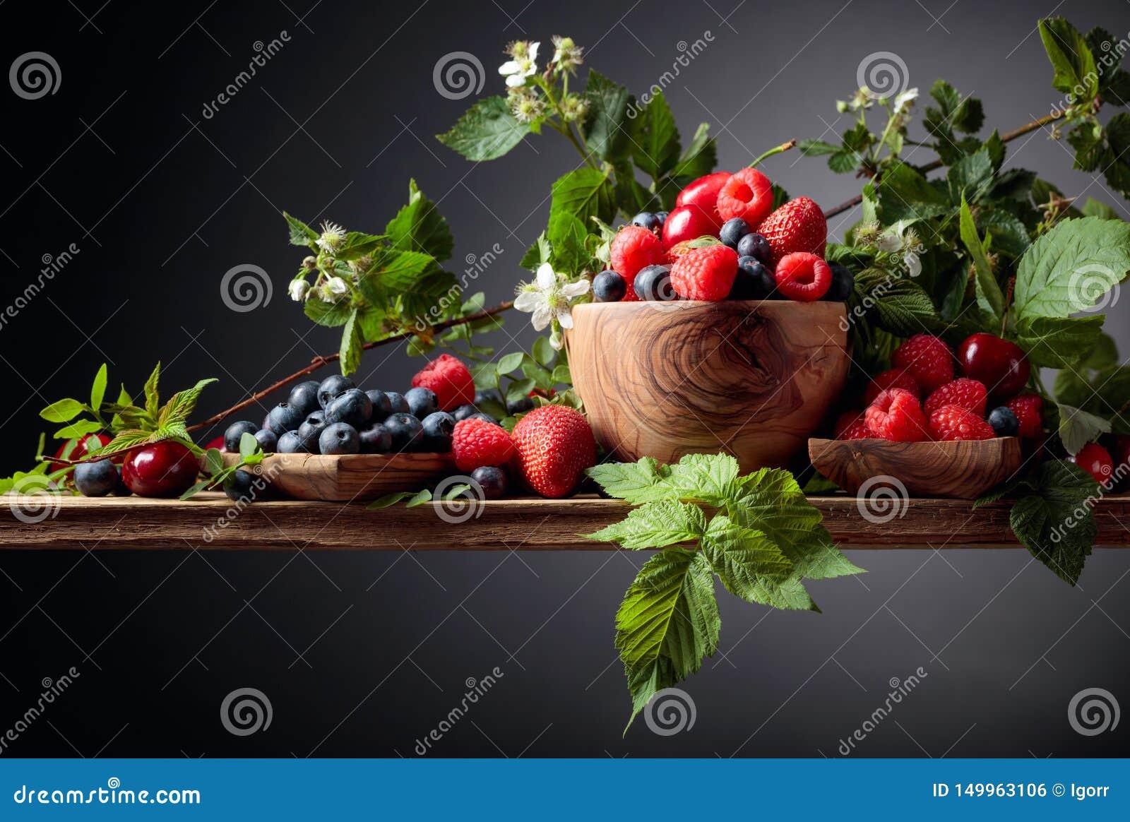 Miscela assortita variopinta del primo piano delle bacche della fragola, del mirtillo, del lampone e della ciliegia su una vecchi