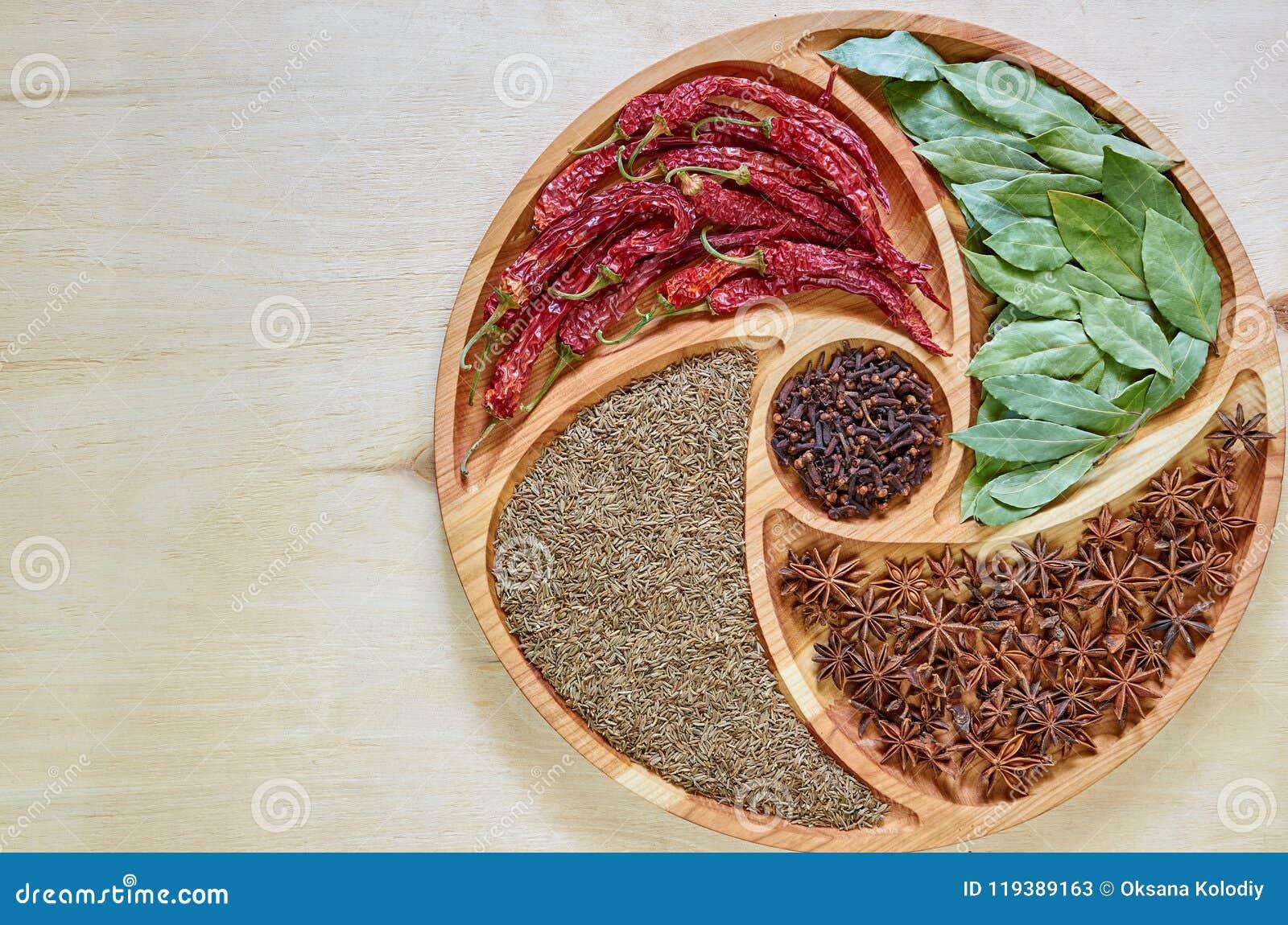 Miscela delle spezie calde sul piatto di legno: anice stellato, foglie della baia, paprica, chiodi di garofano secchi ed alto vic