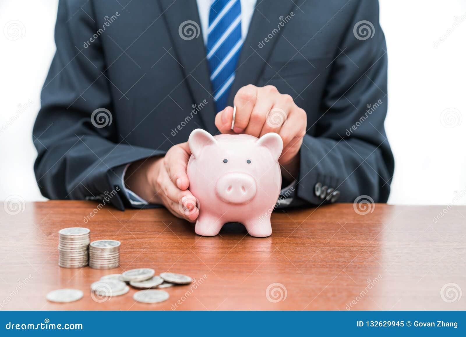 Mise des pièces de monnaie dans le concept porcin de banque-Le de l épargne