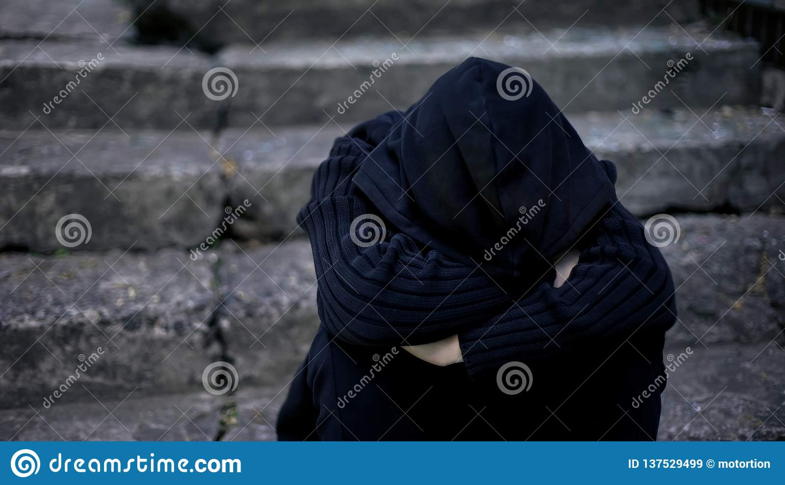 Miserable teenager wrapping in hood, going to sleep on street, depression crisis