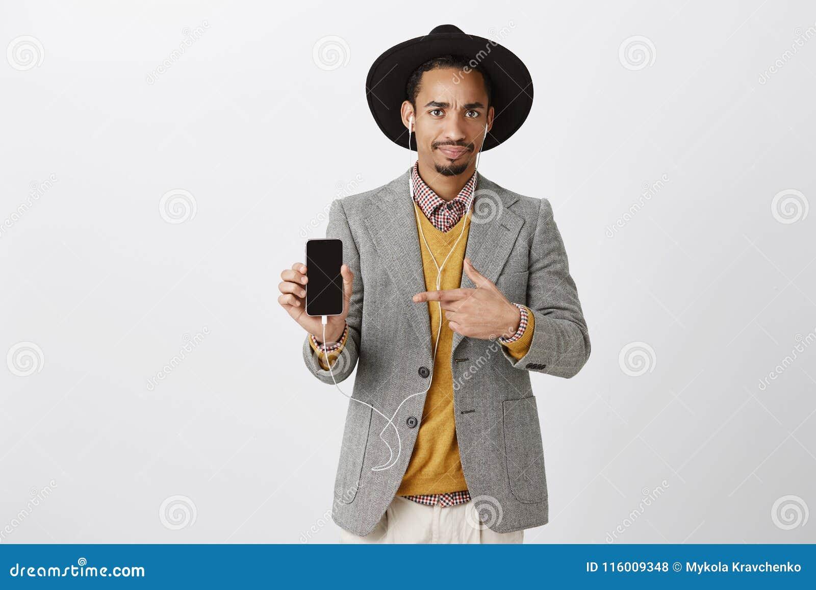 Missnöjd grabb som visar äckligt ting i smartphone Stående av den besvikna snygga stilfulla mannen i svart hatt