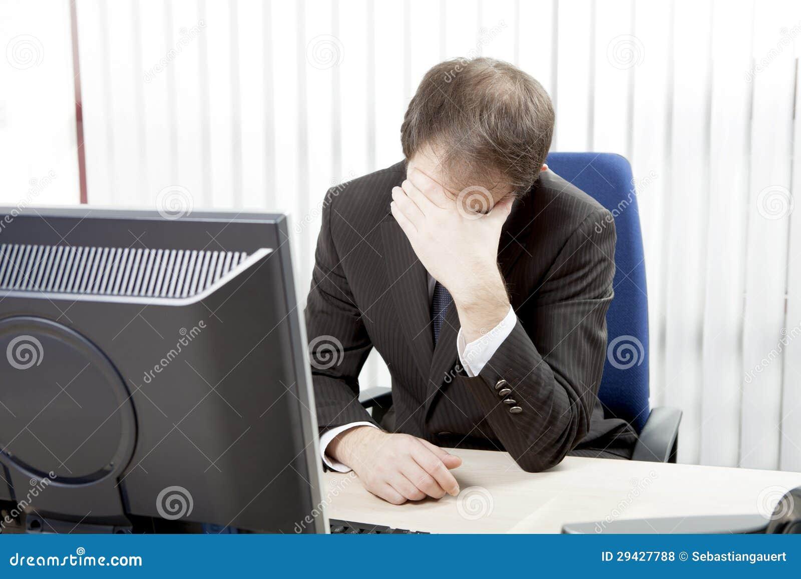 Misströsta affärsman på hans skrivbord
