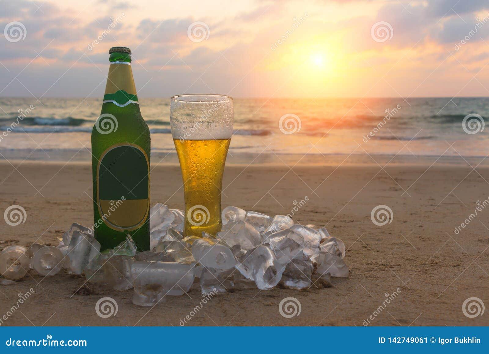 Misted flaska och exponeringsglas av kallt ?l p? sanden av sceniskt p? bakgrunden av seascape, solnedg?nghimmel och havsv?gor