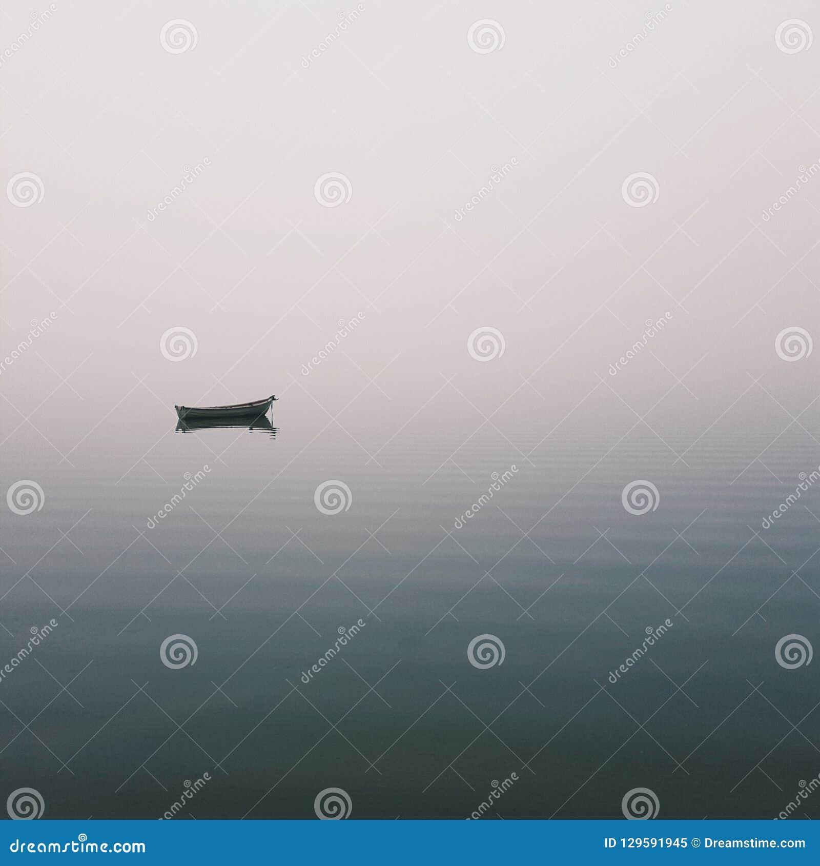 Mistic ensamt fartyg i mitt av sjön, mistdimma