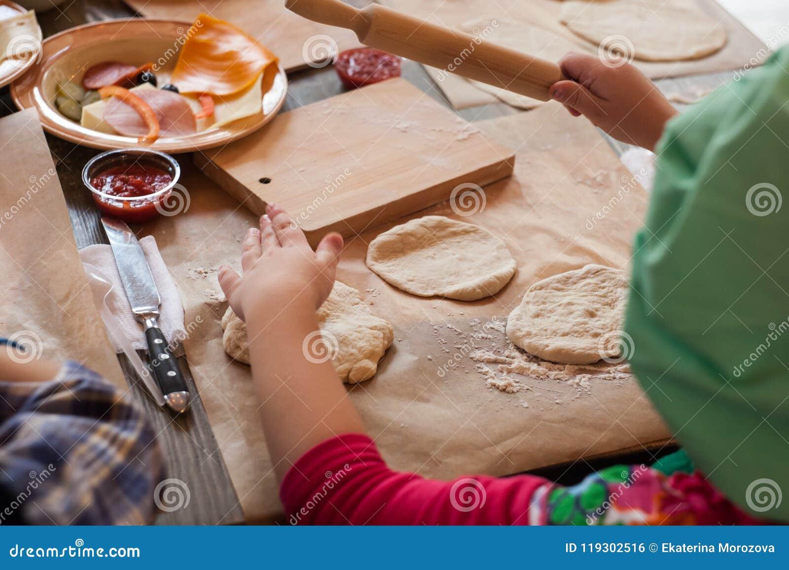 Mistrzowska klasa dla dzieci na piec śmieszną Halloween pizzę Młode dzieci uczą się gotować śmieszną potwór pizzę Dzieciaków przy