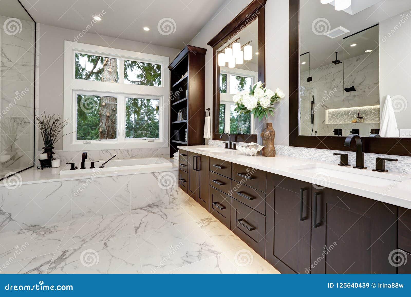 Mistrzowski łazienki wnętrze w luksusowym nowożytnym domu z ciemnymi twarde drzewo gabinetami, białą balią i szkło drzwiową prysz