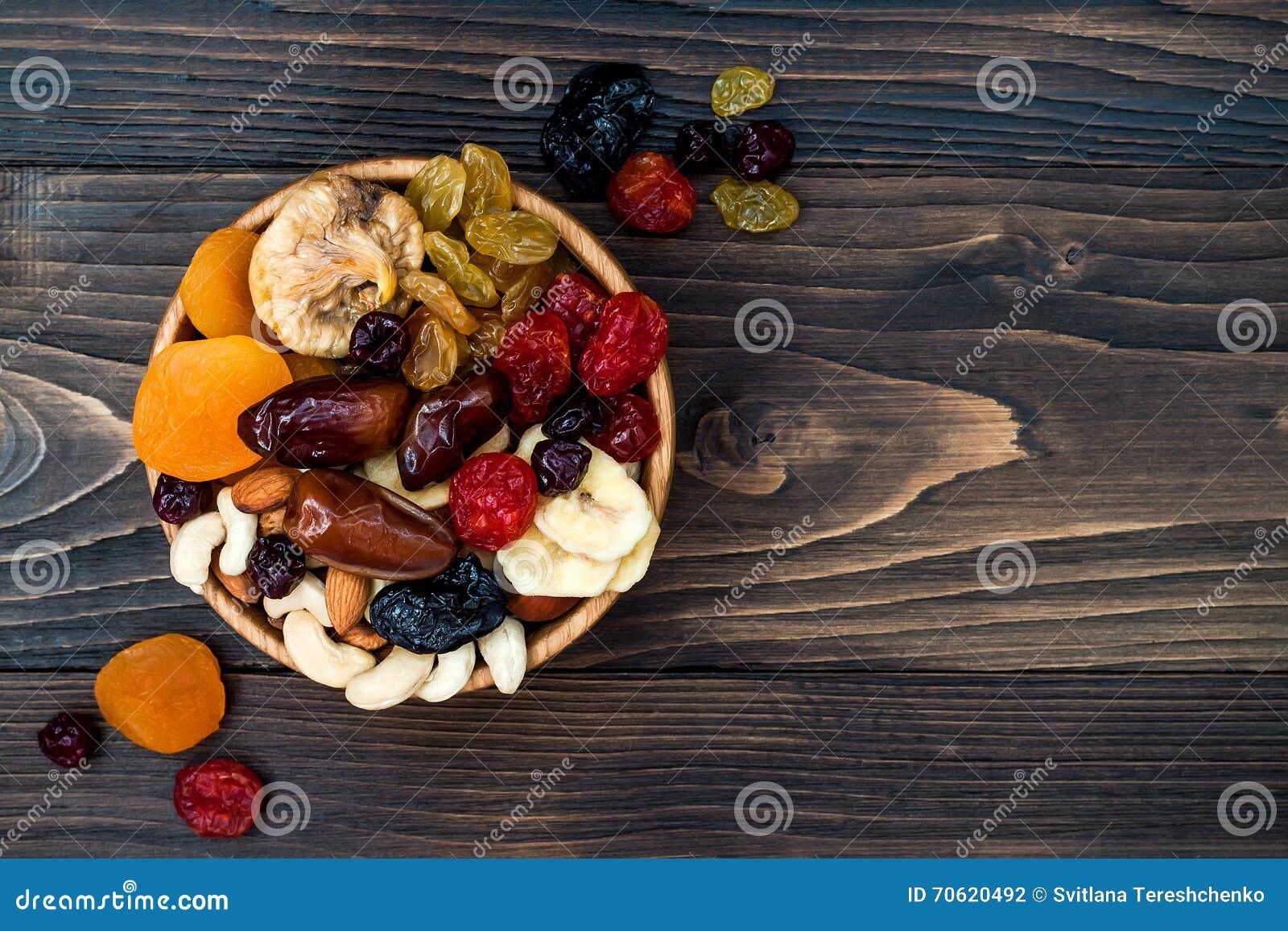 Mistura de frutos e de porcas secados em um fundo de madeira escuro com espaço da cópia Vista superior Símbolos do feriado judaic