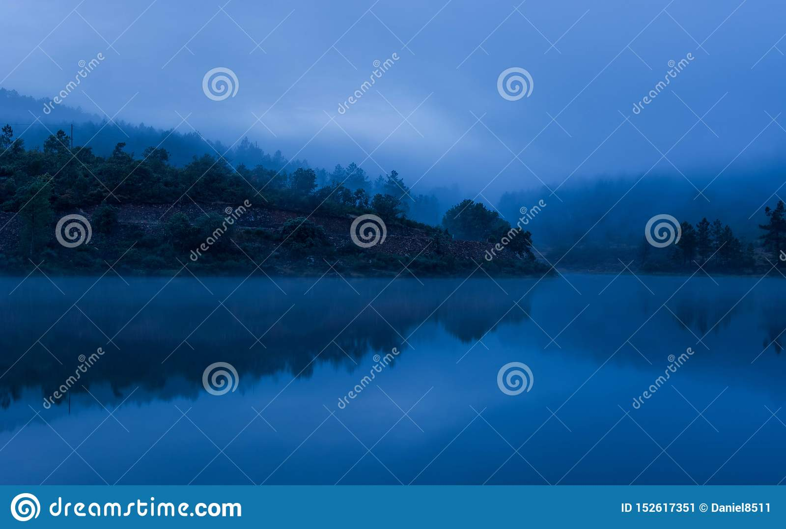 Misty lake with reflections and forest