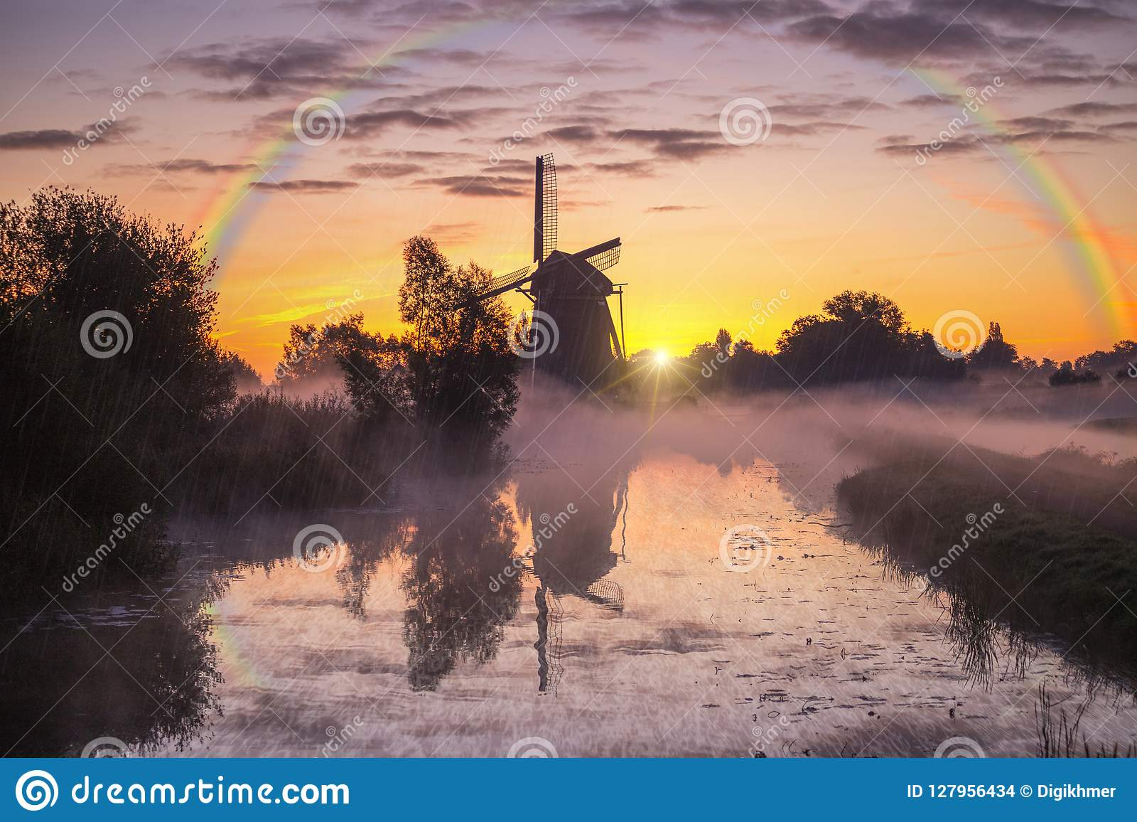 Misty and rainy windmill warm sunrise