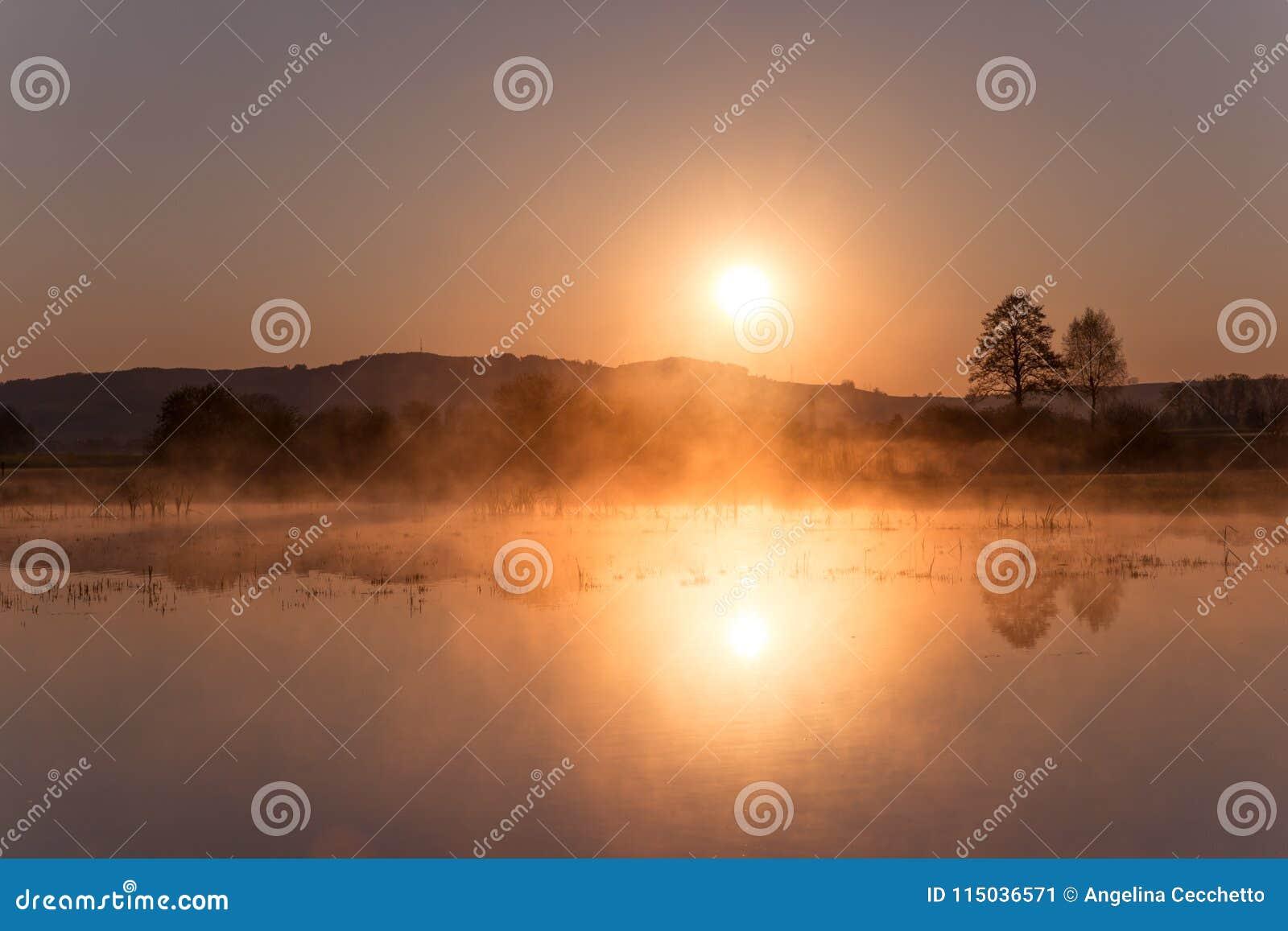 Misty Sunrise Reflecting au-dessus de lac Mauensee au printemps