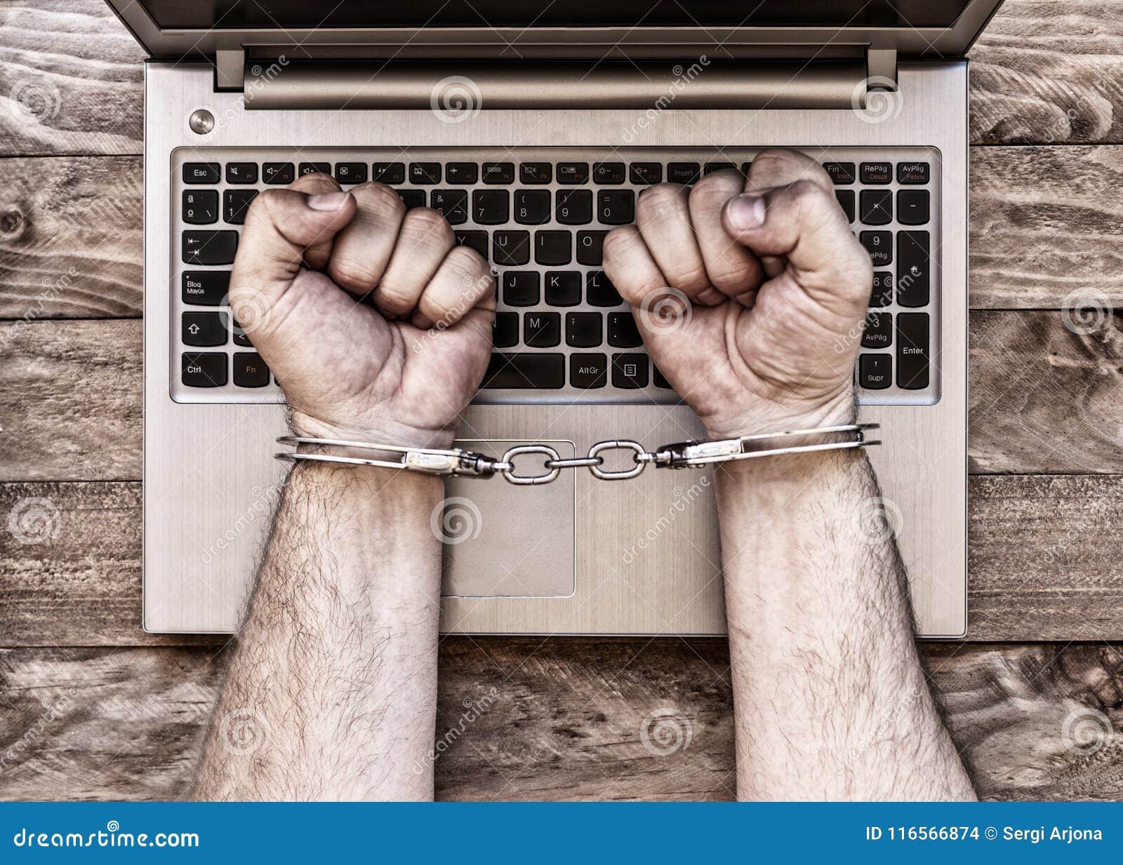 Mit Handschellen gefesselte Hände mit Laptop