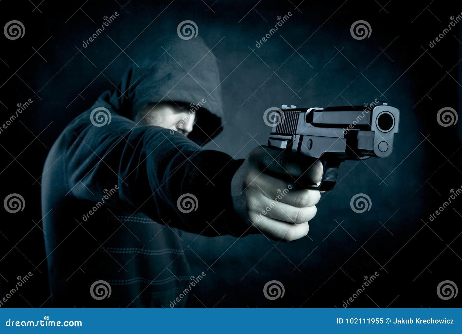 Mit Kapuze Mann mit einem Gewehr in der Dunkelheit