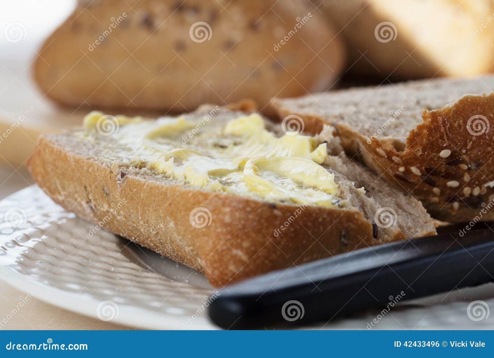 Mitad de Ciabatta de un rollo de pan untado con mantequilla