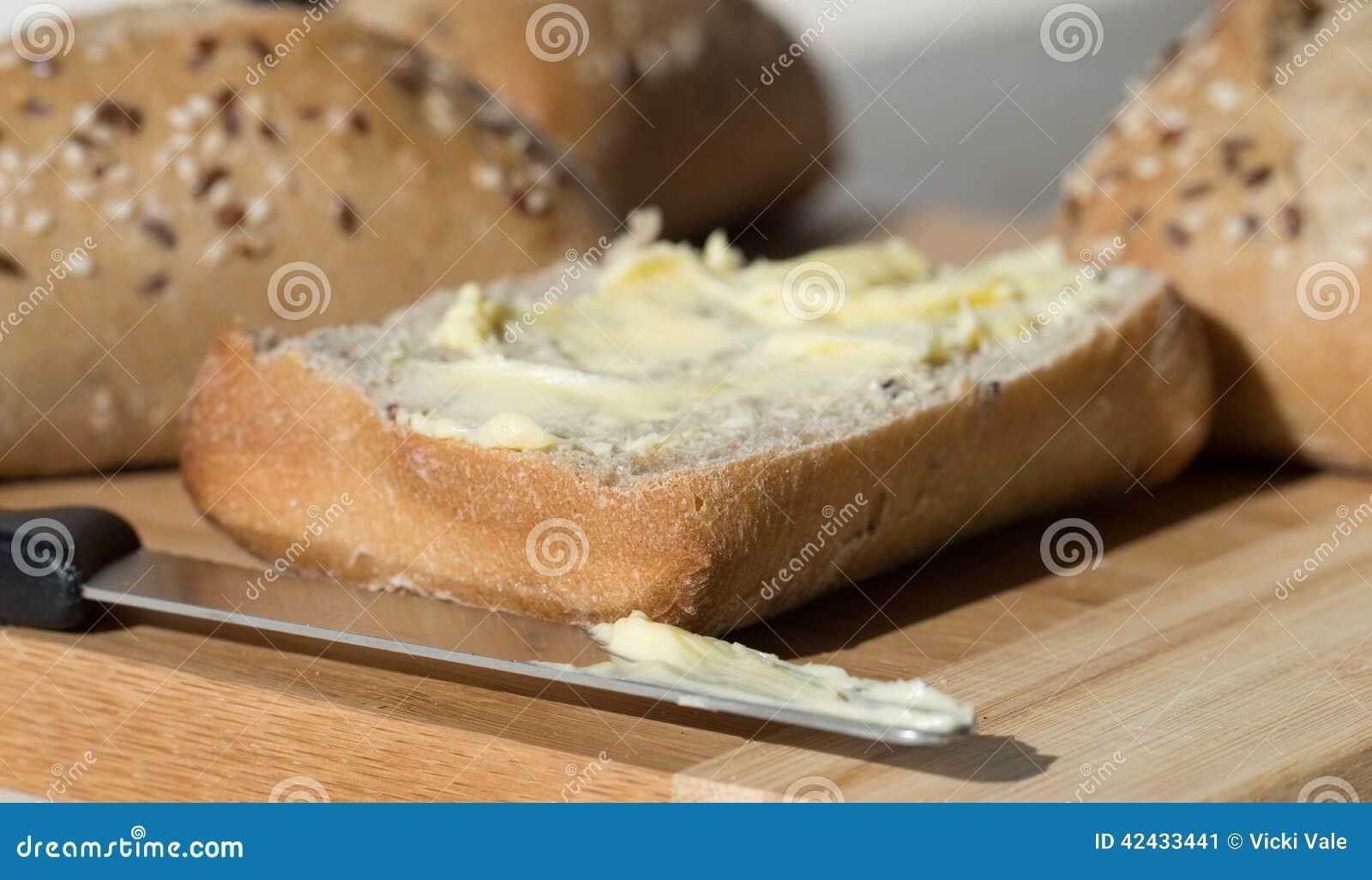 Mitad de Ciabatta de un rollo de pan untado con mantequilla con el cuchillo