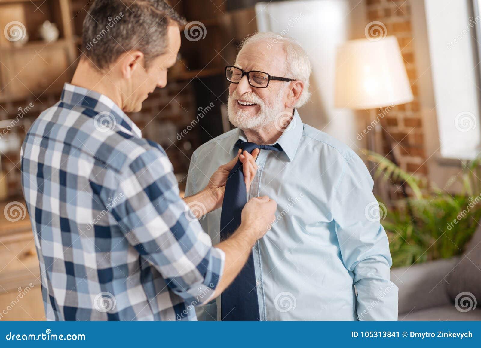 Mitfühlender Mann, der seinem älteren Vater hilft, seins zu binden Bindung