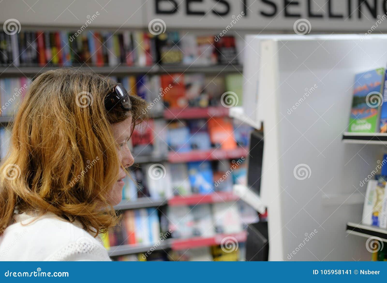 Mitglied dort der Öffentlichkeit, Bücher zu betrachten gesehen, wie in einem Hochstraßenzeitschriftenhändler und -buchhandlung ge