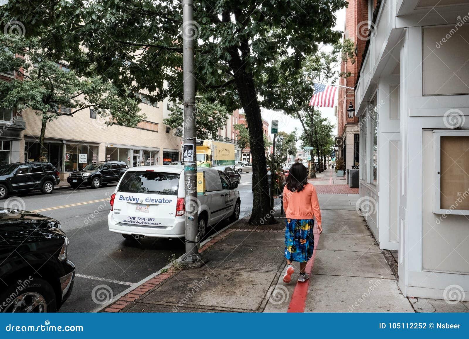 Mitglied von ihm Öffentlichkeit gesehenes Gehen hinunter eine Straße in einer Neu-England Stadt