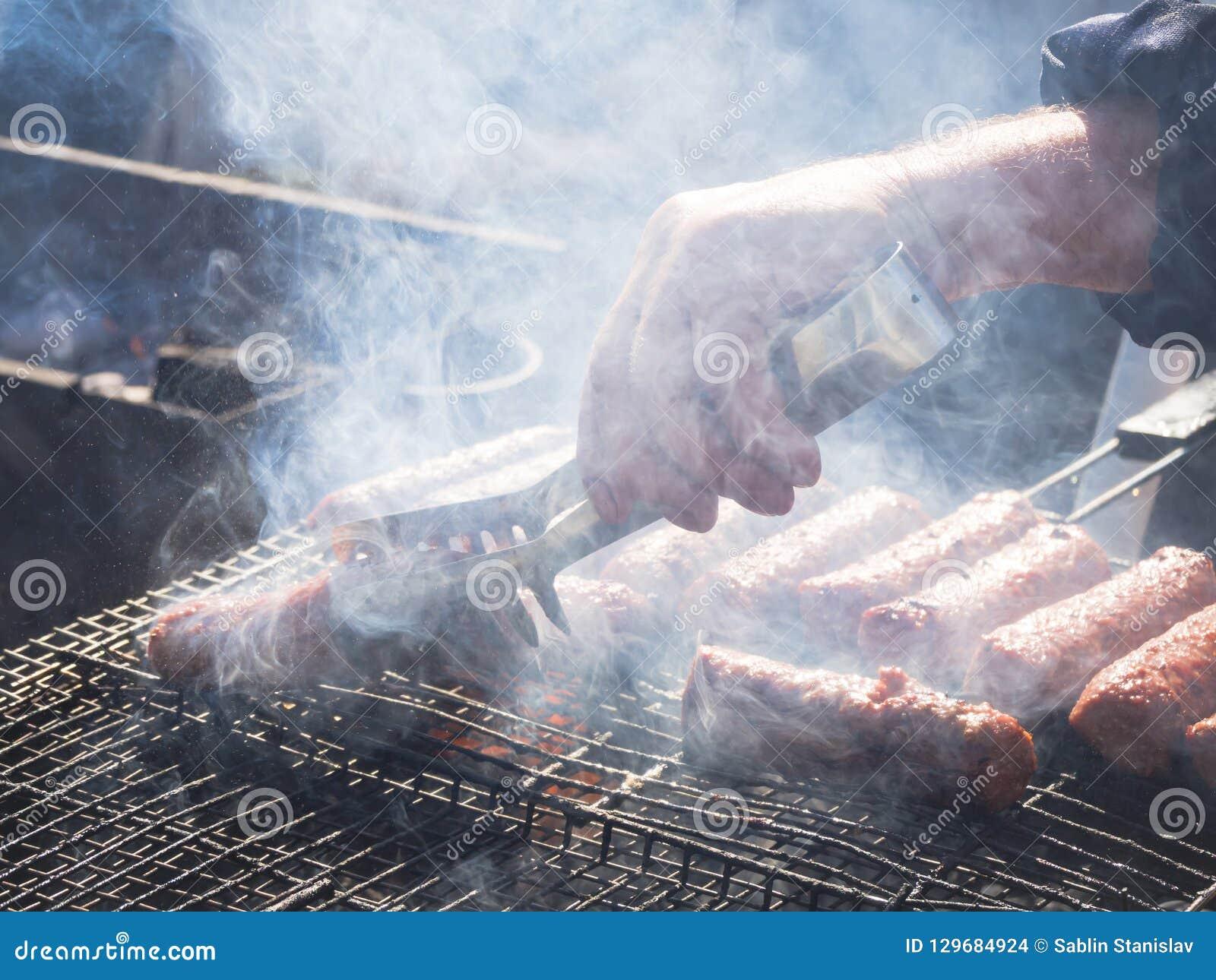 Mititei romeno e cozinhado na grade no fumo