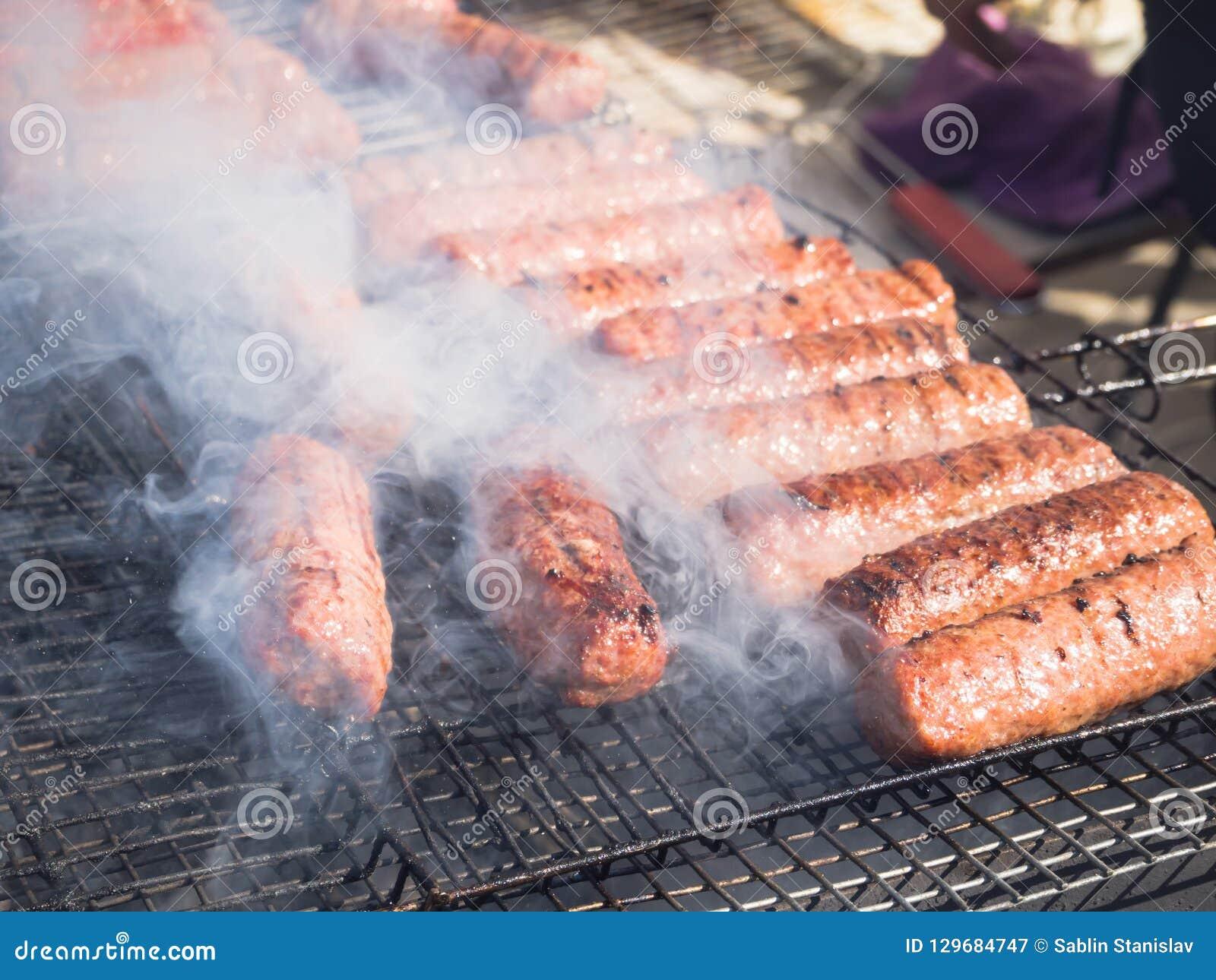 Mititei rumeno e cucinato sulla griglia nel fumo