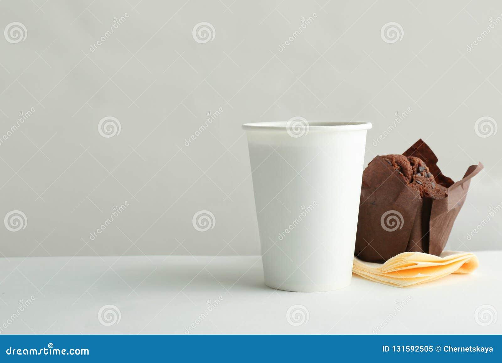 Mitnehmerpapierkaffeetasse und geschmackvolles Muffin auf weißem Hintergrund
