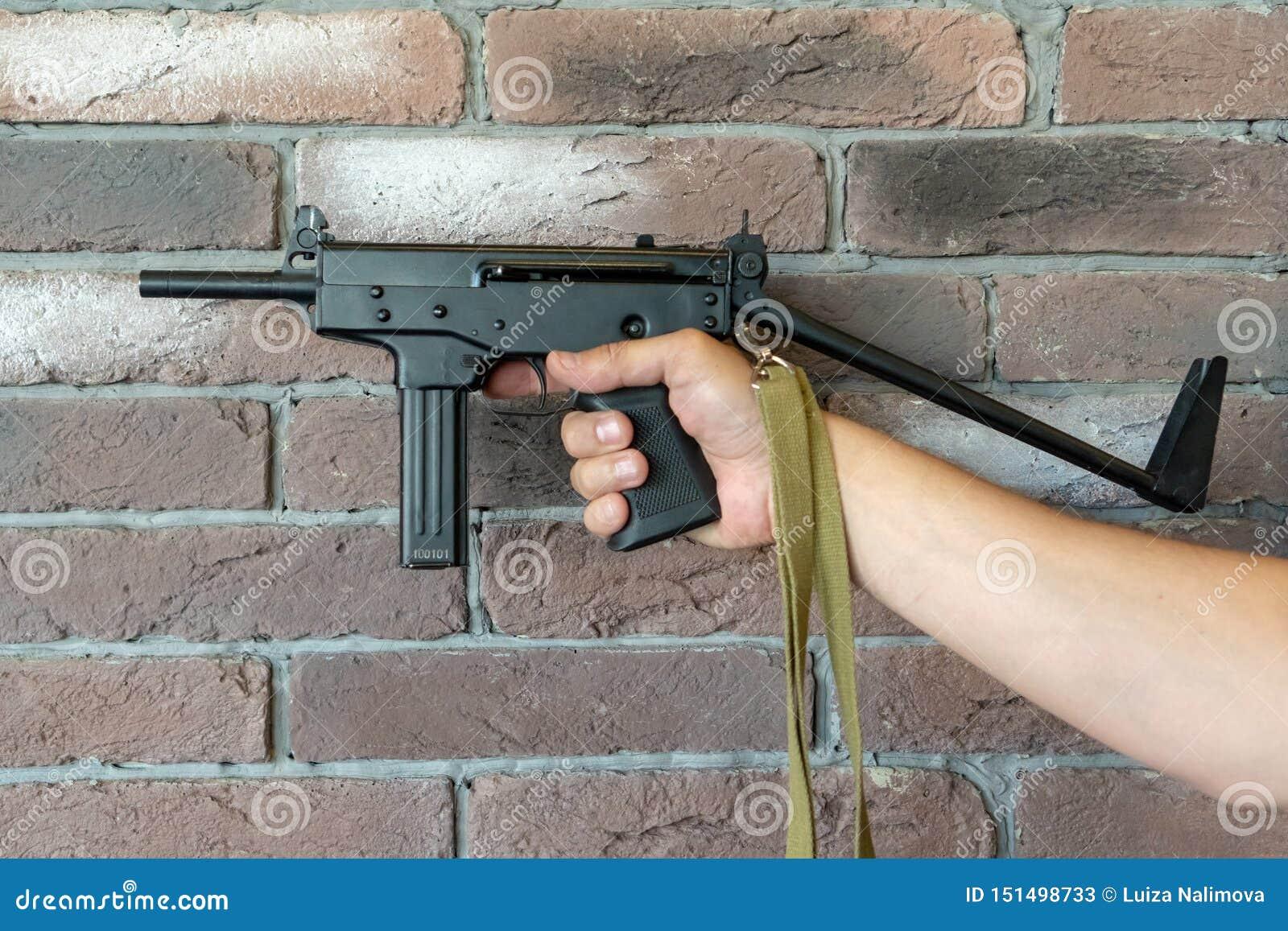 Mitragliatrice leggera di PP-91 Kedr Un uomo tiene una mitragliatrice in sua mano sui precedenti di un muro di mattoni marrone
