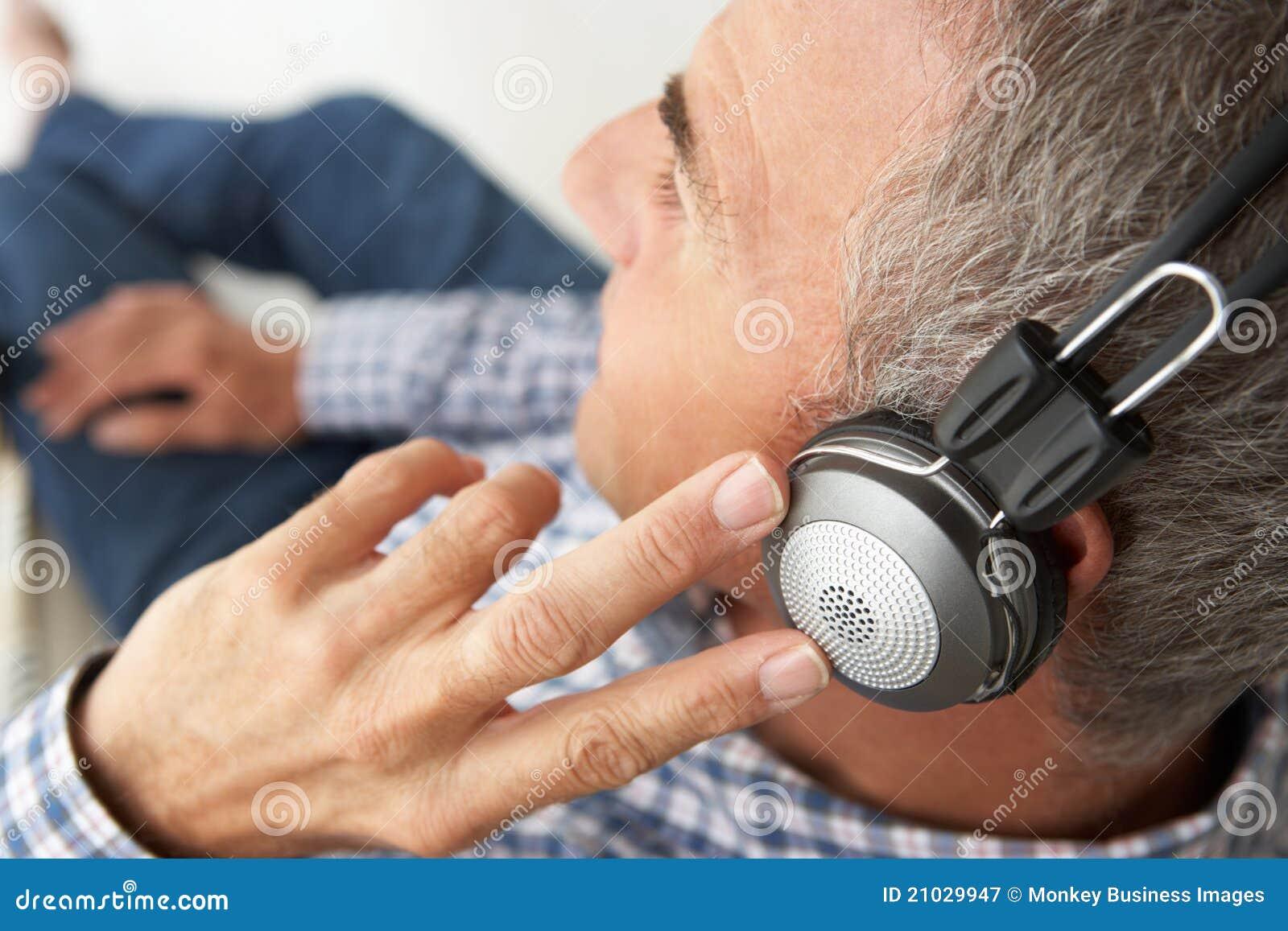 Mitt- ag-man som lyssnar till musik till och med hörlurar