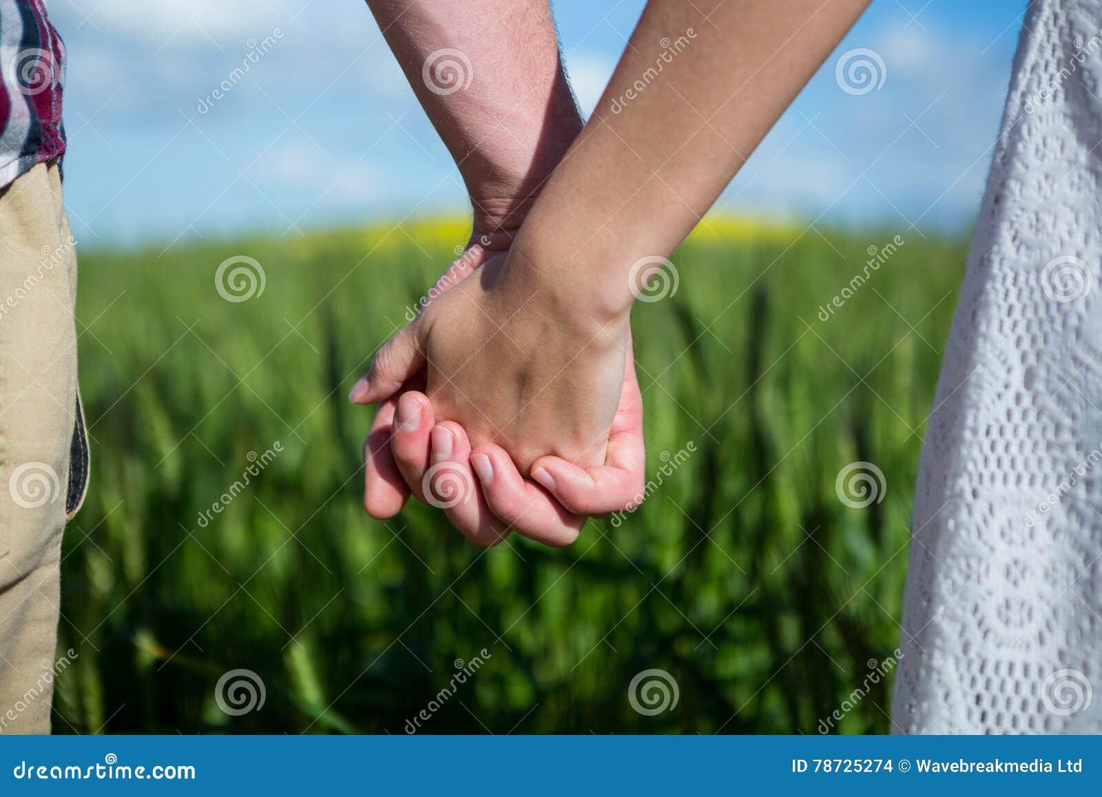 Mitt- avsnitt av parinnehavhänder i fält