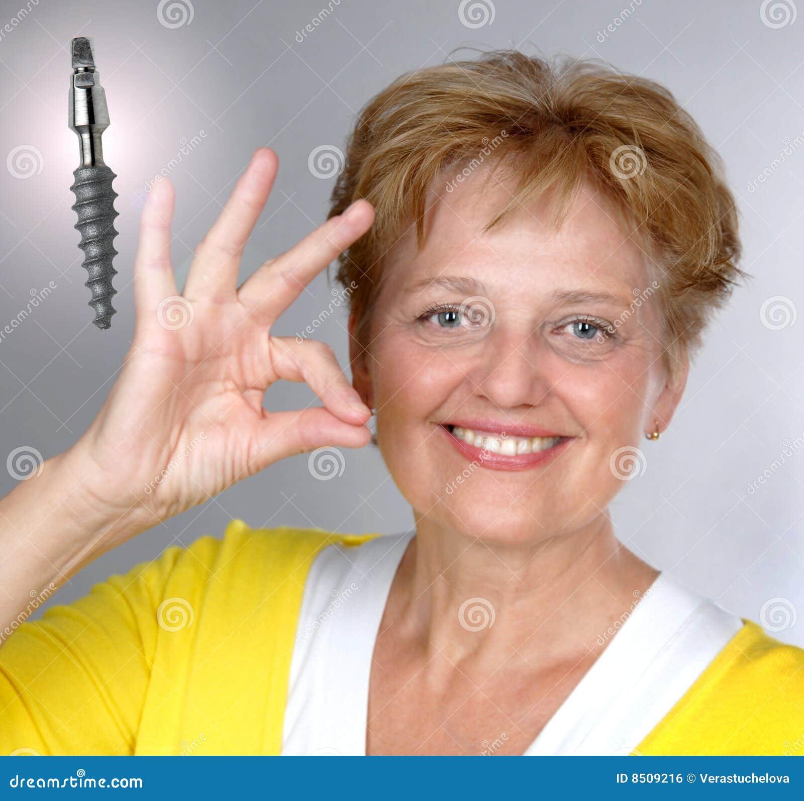 Mitt- gammal tillfredsställd kvinna för åldrig implantat