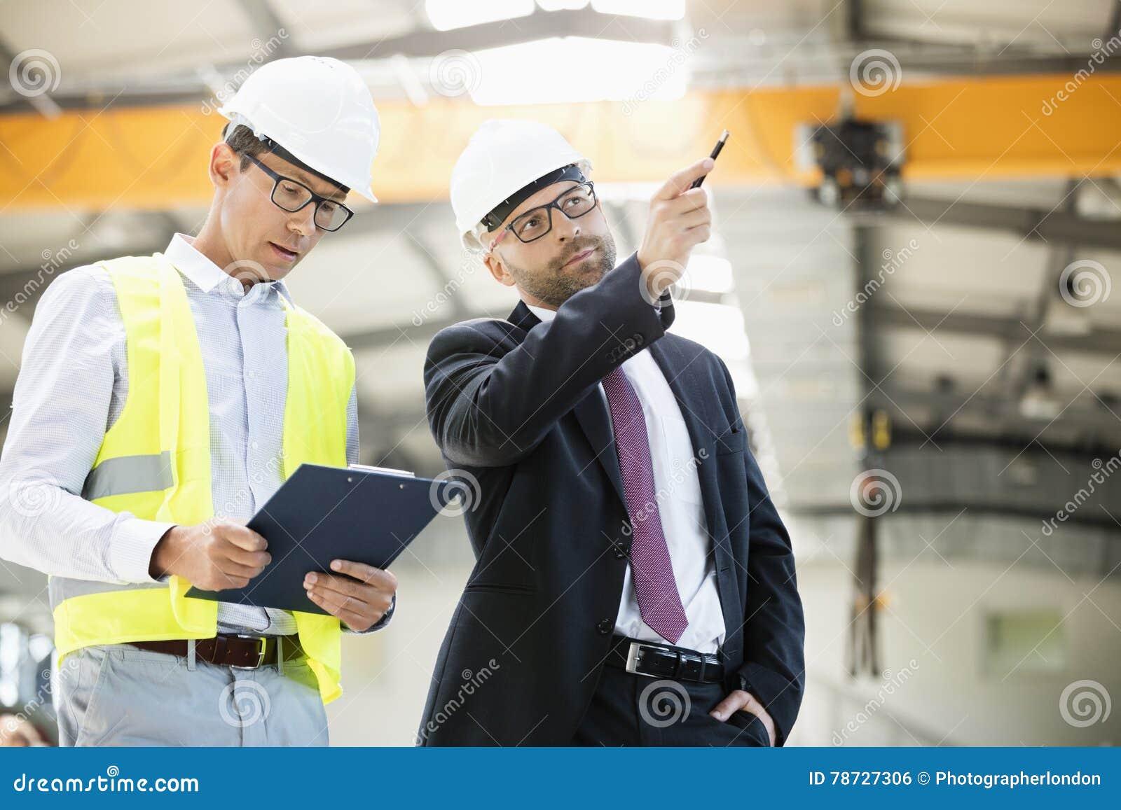 Mitt- vuxen affärsman med arbetsledaren som har diskussion i metallbransch