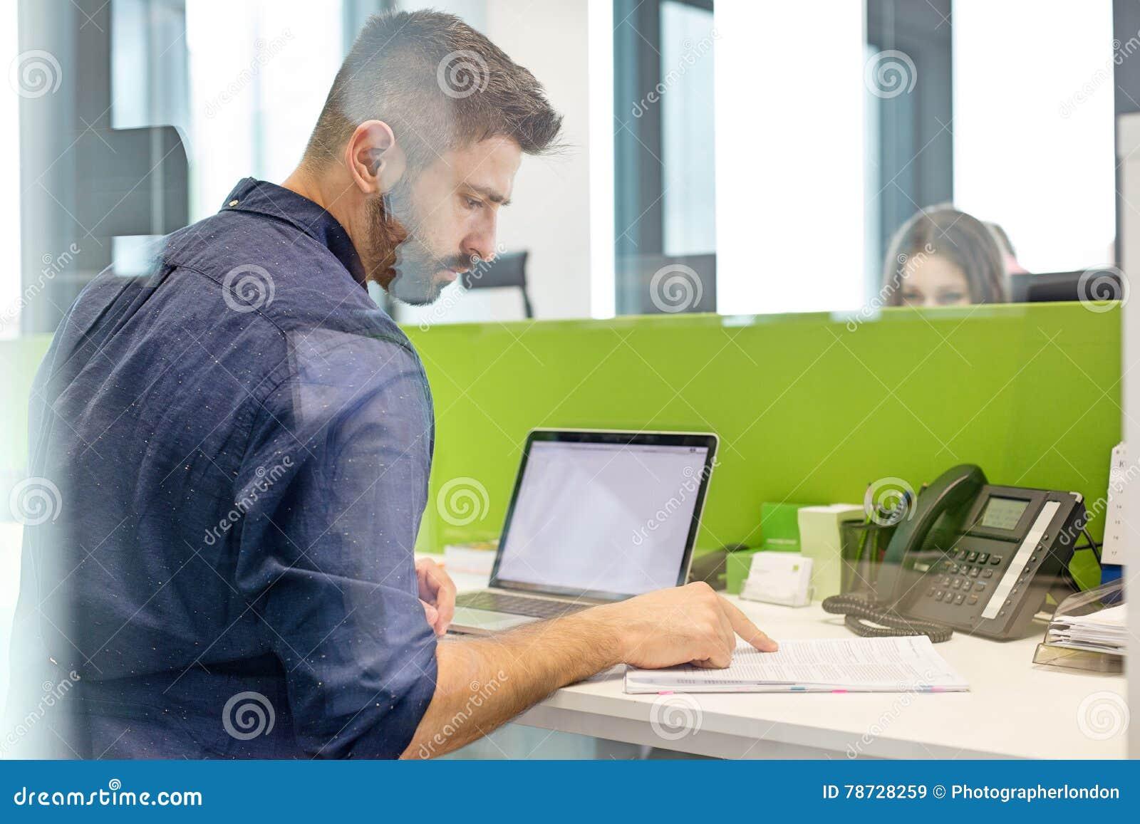 Mitt- vuxen affärsman med bärbar datorläseboken på skrivbordet i regeringsställning