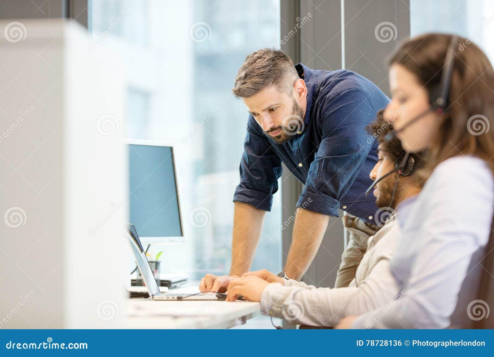 Mitt- vuxen affärsman som använder bärbara datorn med coworkers som i regeringsställning bär hörlurar med mikrofon