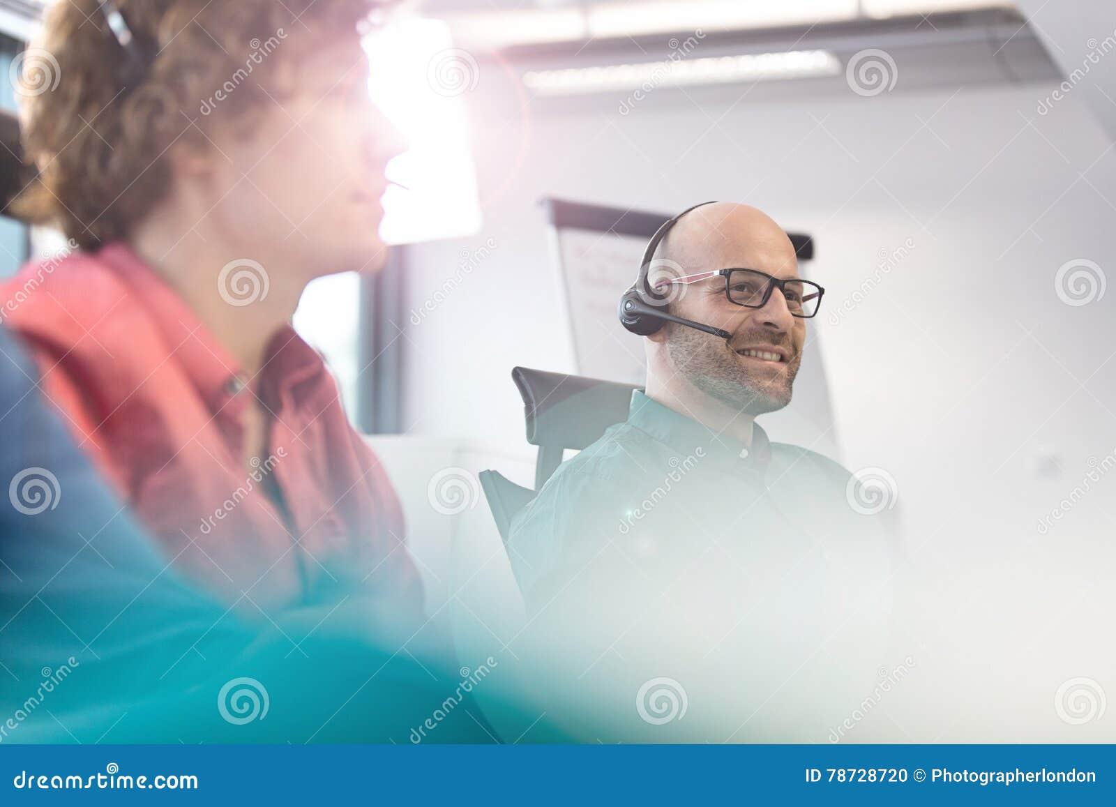 Mitt- vuxen affärsman som använder hörlurar med mikrofon med manliga kollegor i förgrund på kontoret