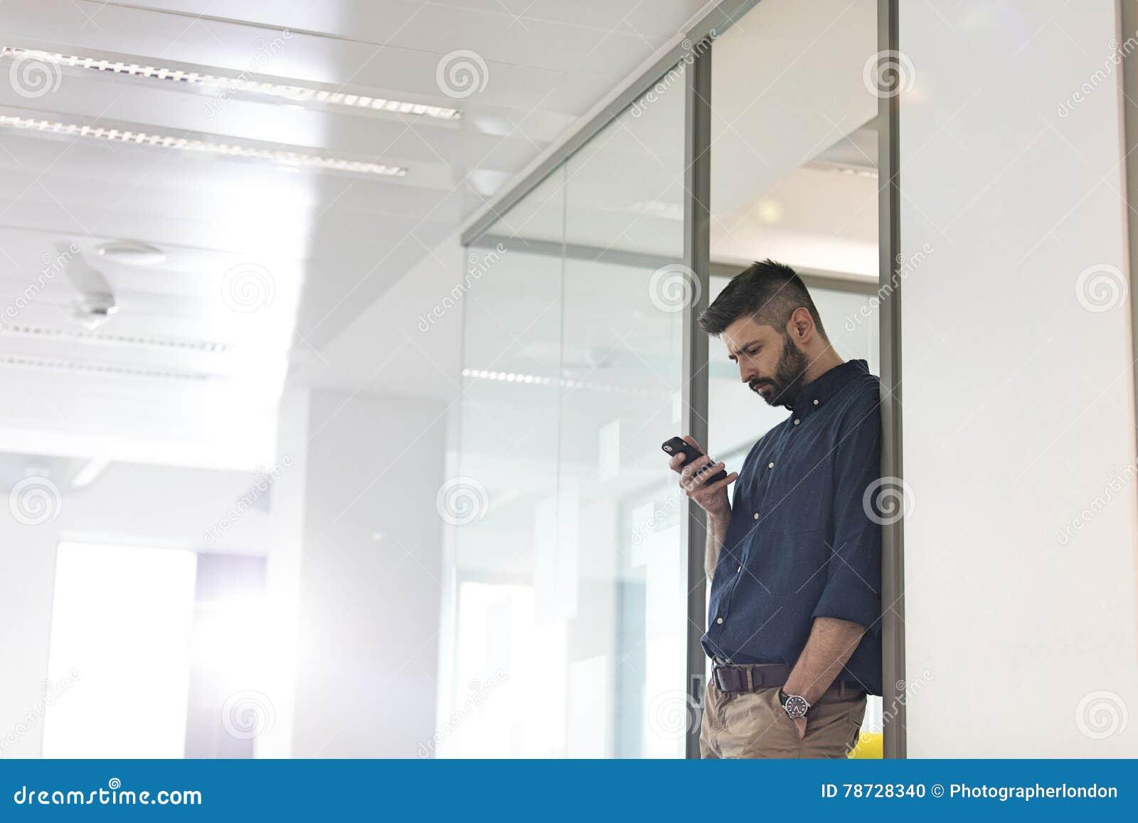 Mitt- vuxen affärsman som i regeringsställning använder mobiltelefonen