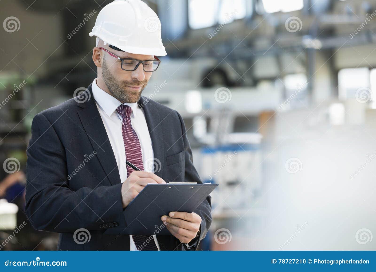Mitt- vuxen affärsmanhandstil på skrivplattan i metallbransch