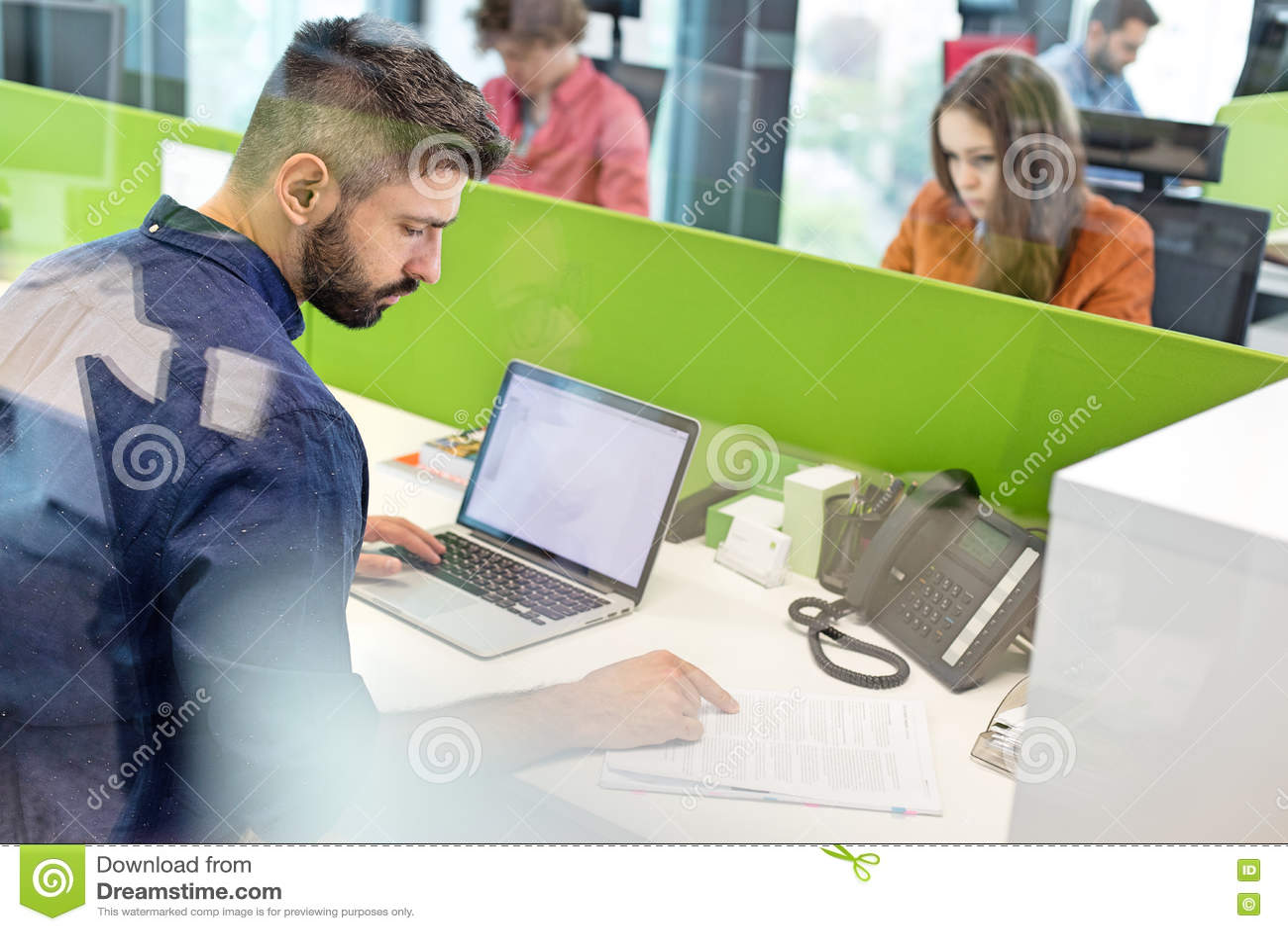 Mitt- vuxen affärsmanläsebok, medan genom att använda bärbara datorn i regeringsställning