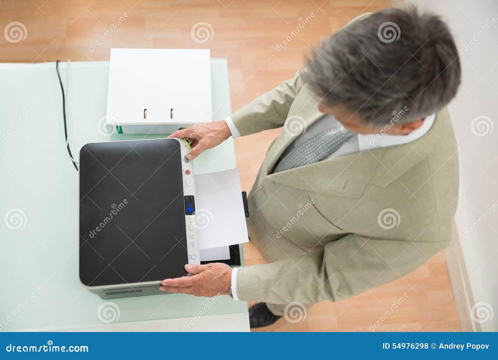 Mitt--vuxen människa affärsman som använder fotokopiamaskinen