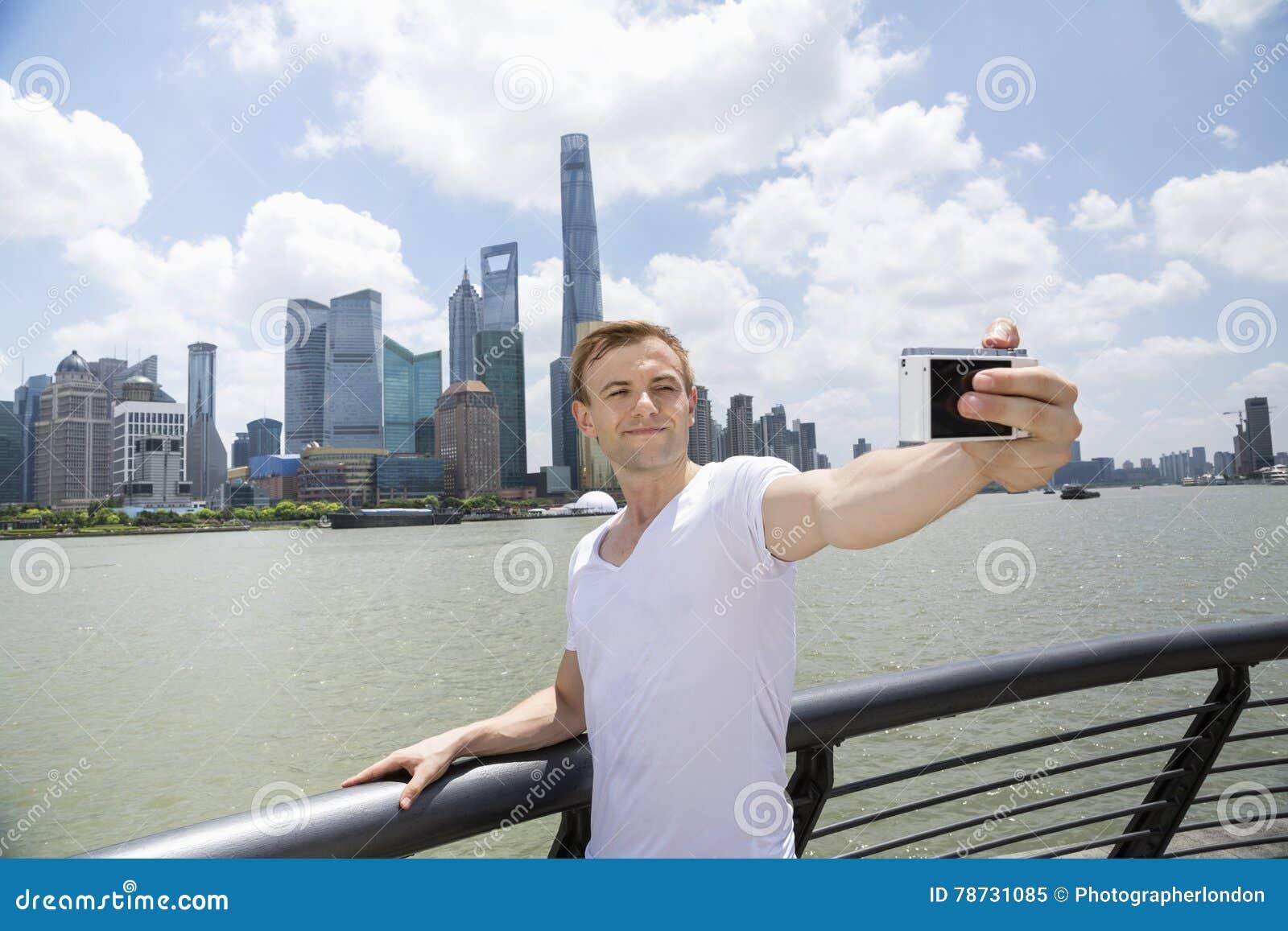 Mitt- vuxen man som tar selfie, medan stå vid räcket mot Pudong horisont