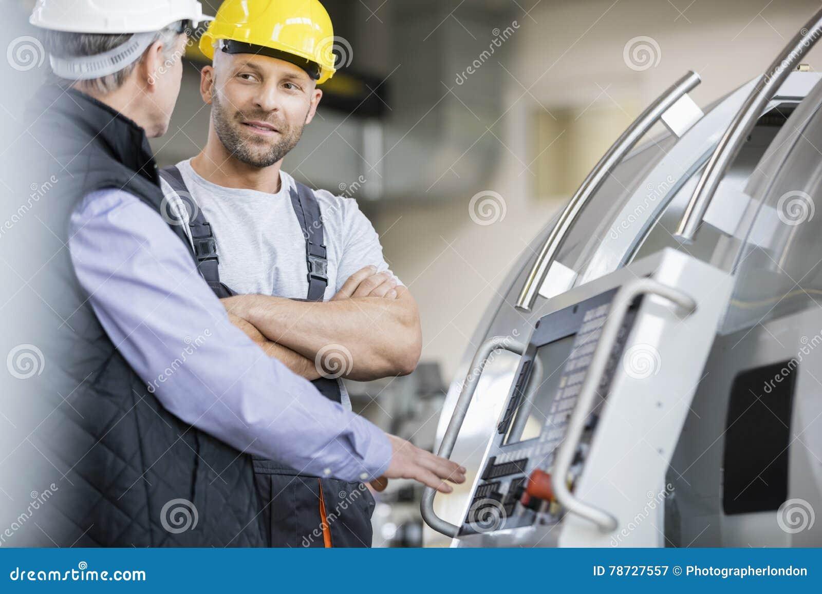 Mitt- vuxen manuell arbetare som har diskussion med kollegan vid maskineri i bransch