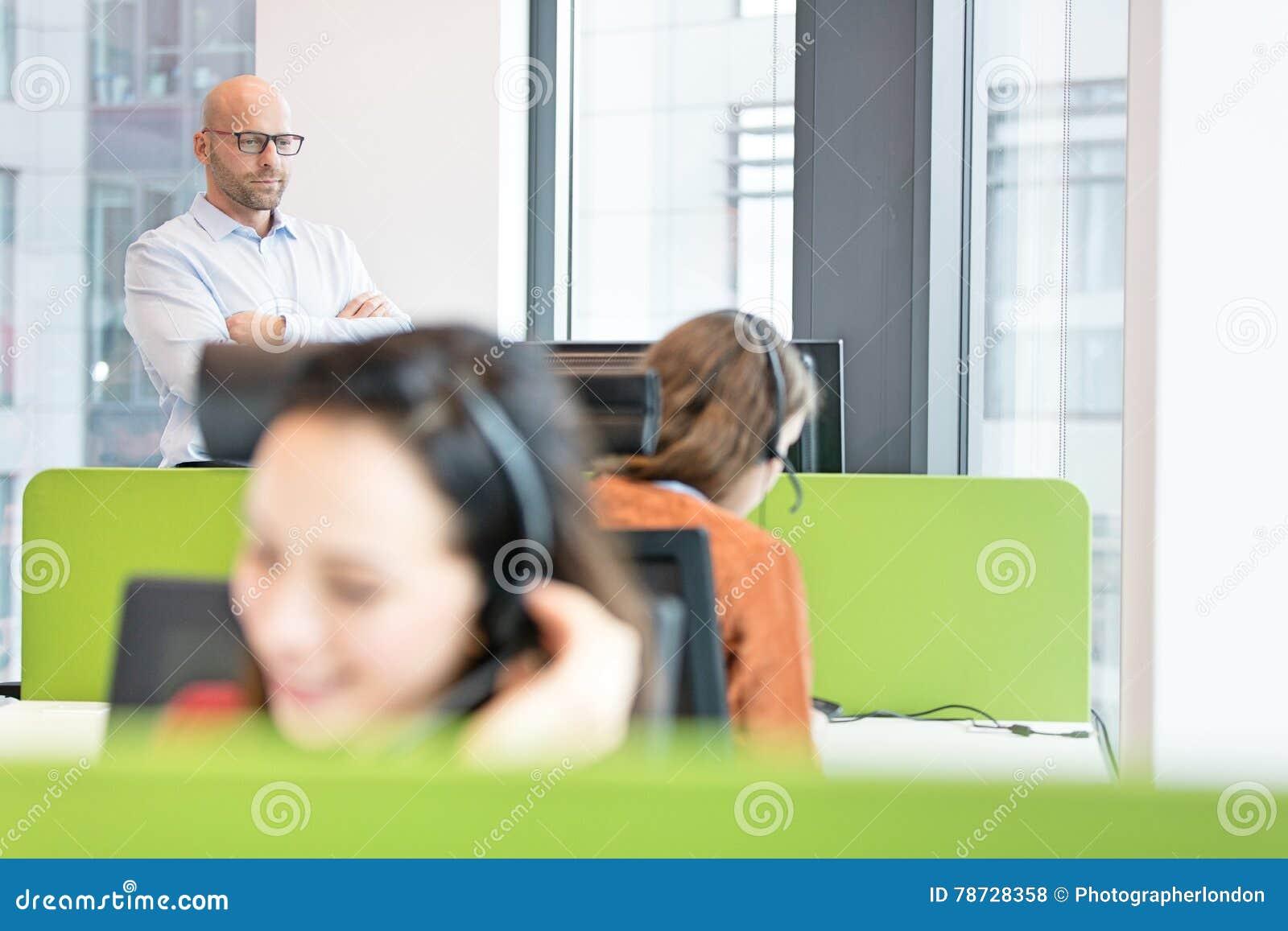 Mitt- vuxna affärsmananseendearmar korsade med kvinnliga kollegor som arbetar i förgrund på kontoret