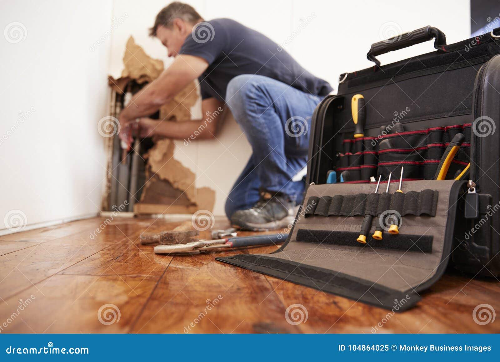 Mitte gealterter Mann, der gesprengtes Rohr, Klempnerarbeit, Fokus auf Vordergrund repariert