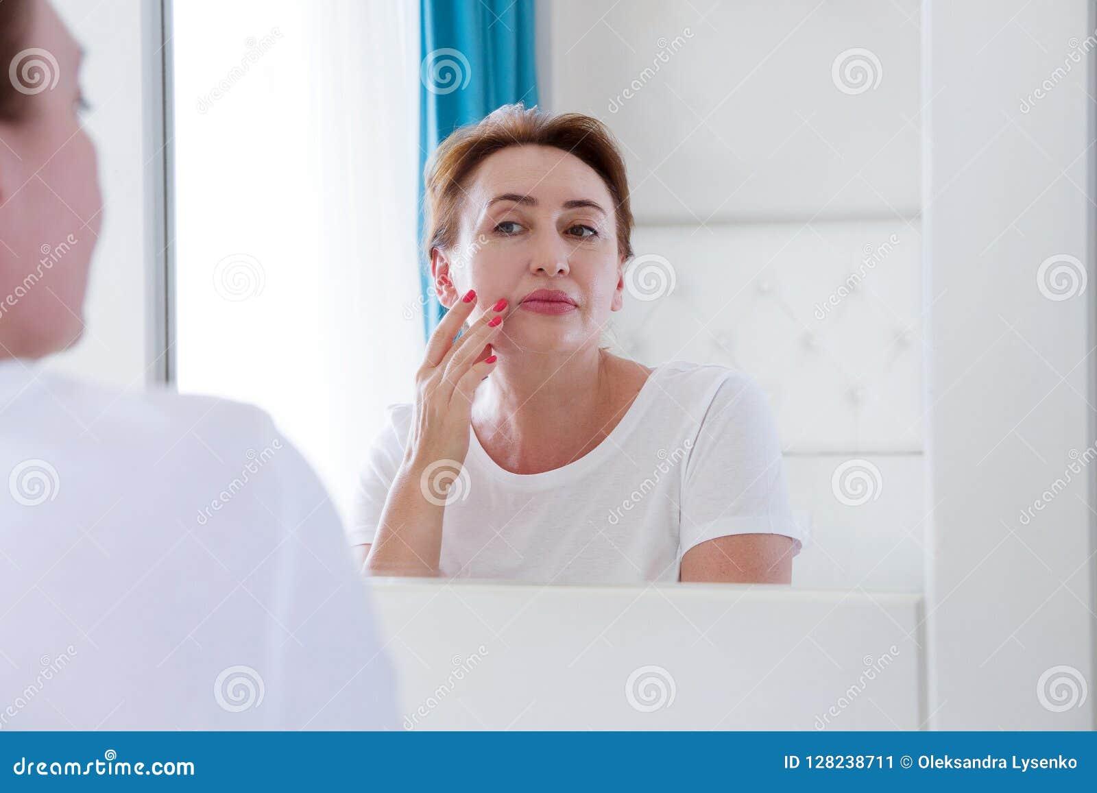 Mittelalterfrau, die im Spiegel auf Gesicht mit Beuteln unter den Augen schaut Falten, Antialternhautpflegekonzept Selektiver Fok
