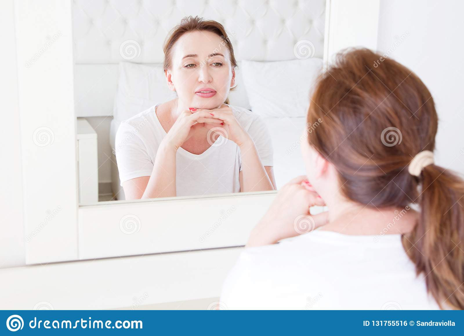 Mittelalterfrau, die im Spiegel auf Gesicht schaut Falten und Antialternhautpflegekonzept Selektiver Fokus