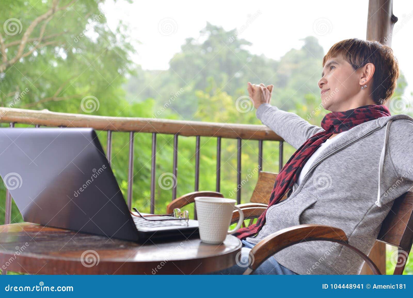 Mittelalterfrau, die mit Laptop-Computer sich entspannt