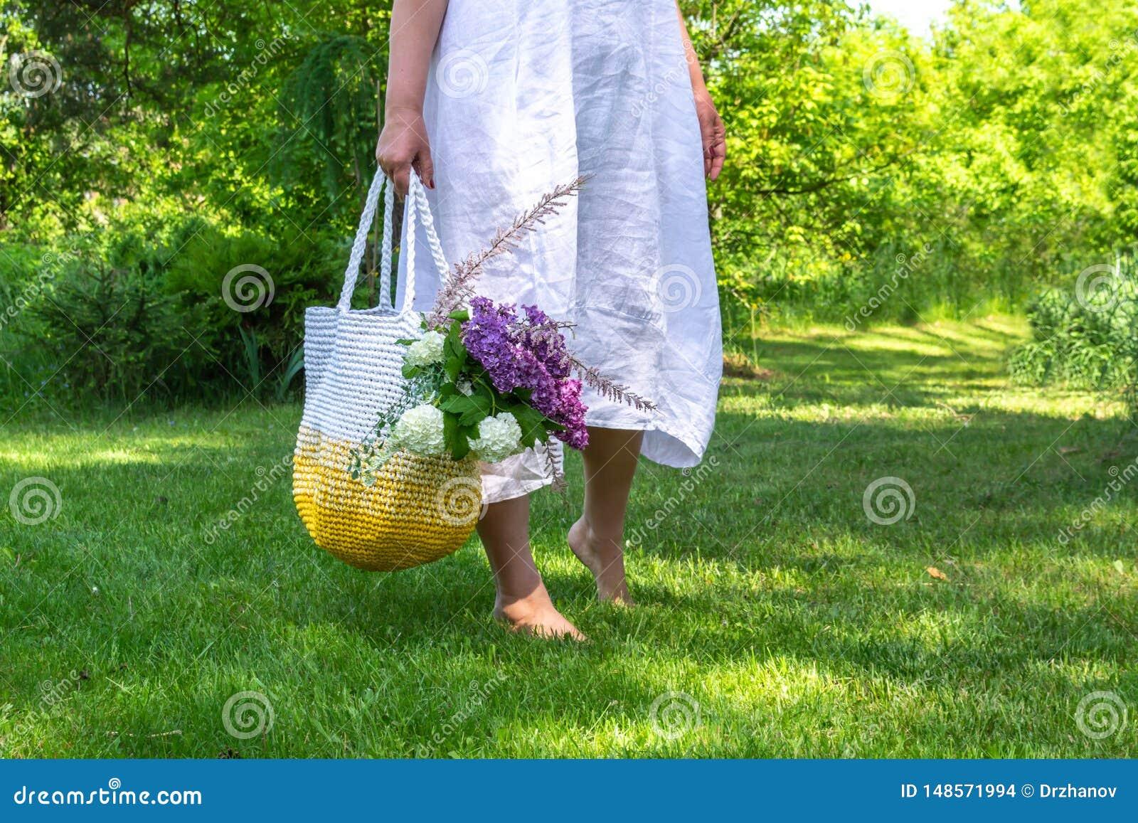 Mittelalterfrau im weißen einfachen Leinenkleid bleibt barfuß auf dem Gras im schönen Garten und hält gestrickte weiß-gelbe Tasch