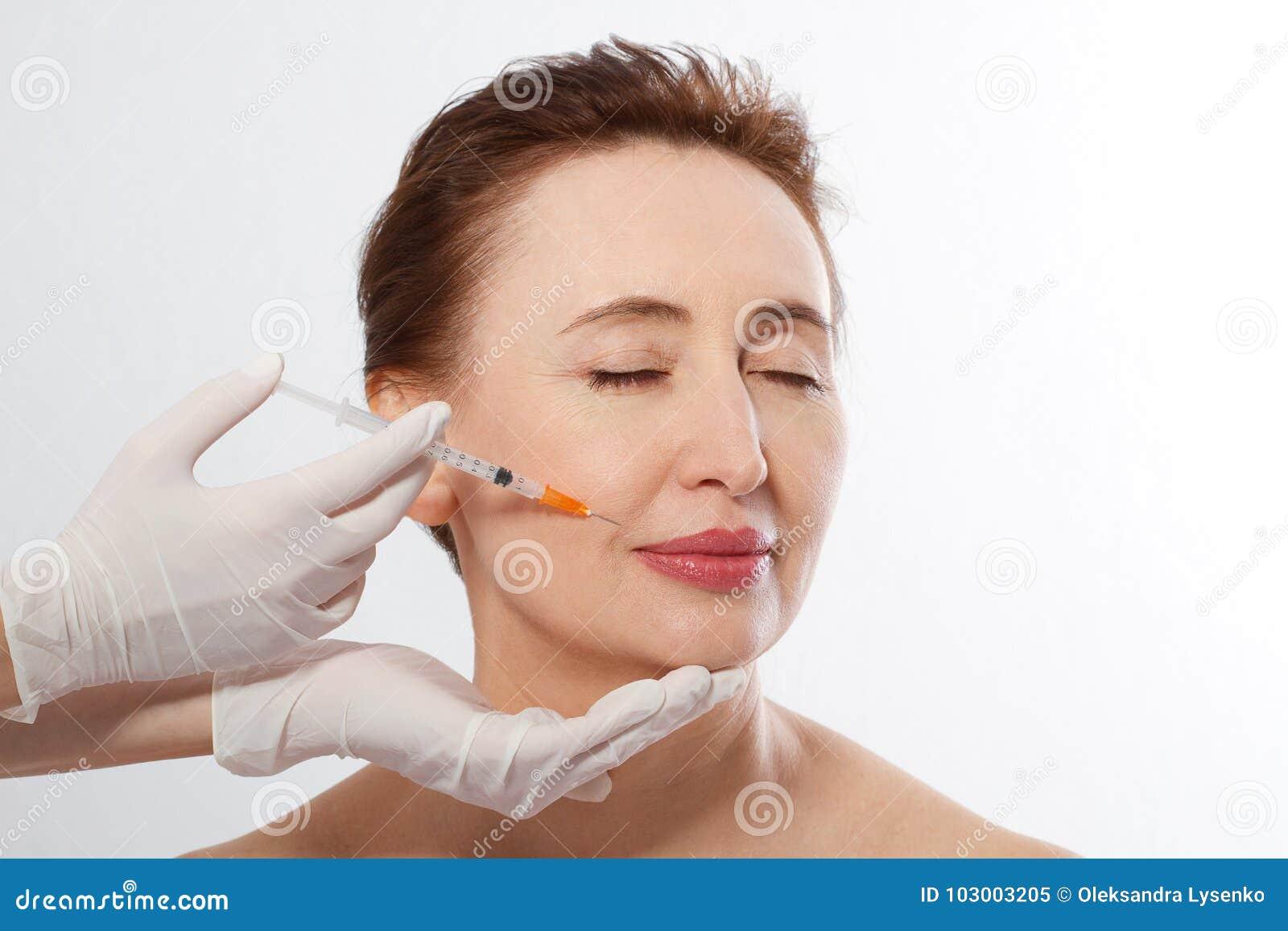 Mittelalterfrau 40s, die anhebende botox Einspritzung in den Lippen durch Doktor lokalisiert auf weißem Hintergrund erhält Makro
